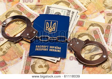 International Ukrainian passport with US dollars and handcuffs on Hryvna banknotes background