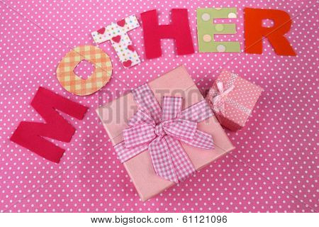 Mother- lettering of handmade paper letters on pink polka background