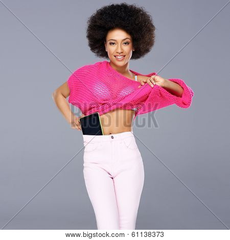 Vivacious chic African American woman with a wild afro hairdo posing in a glamorous see through pink top with a tablet tucked into the waistband of her slacks smiling at the camera