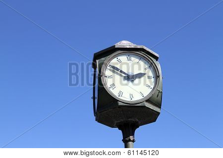 Street clock close-up face on the sky background