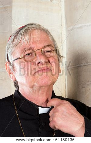 Clergyman being annoyed by the pinching priest collar of his shirt or cassock