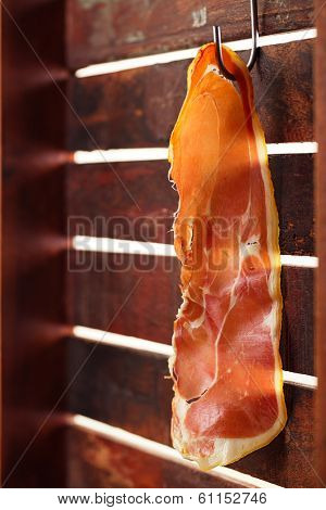 piece of serrano ham jamon Cured Meat hanged on hook