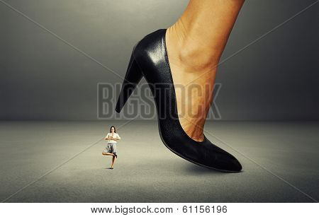 calm smiley businesswoman under big heel over dark background