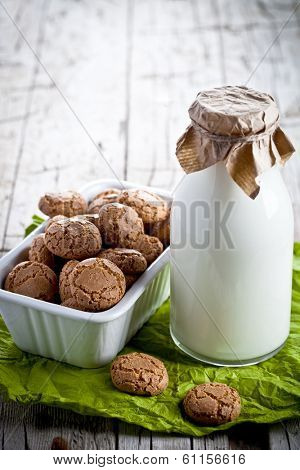meringue almond cookies in a bowl and bottle of milk on wooden background