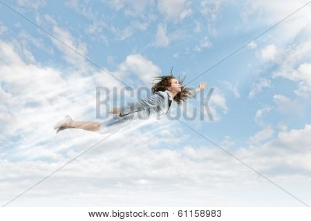 Young happy businesswoman flying high in sky