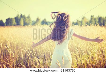 Beauty Girl Outdoors enjoying nature. Beautiful Teenage Model girl in white dress running on the Spring Field, Sun Light.