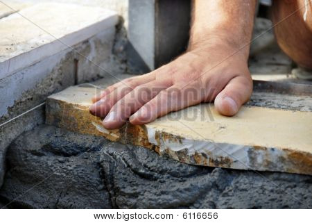 Worker Hand On Flagstone