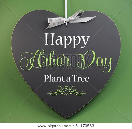 Happy Arbor Day, Plant A Tree, Greeting Message Sign On Heart Shaped Blackboard Against A Green Back