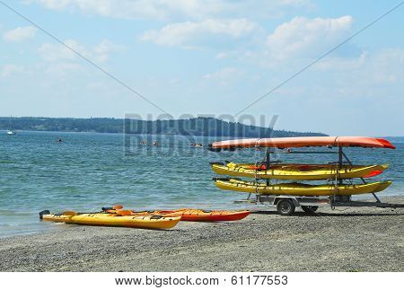 Sea kayaks ready for tourists on land bridge on low tide between Bar Harbor and Bar Island