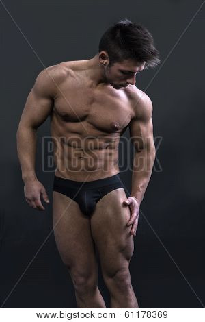 Muscular Shirtless Young Man Touching His Thigh