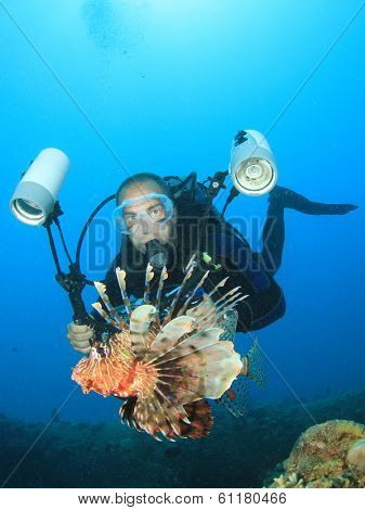 Underwater Photographer scuba diving with lionfish