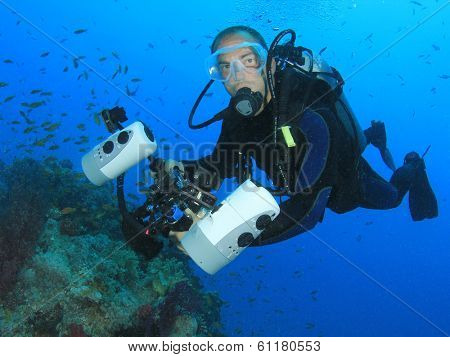 Underwater Photographer scuba diving with DSLR camera
