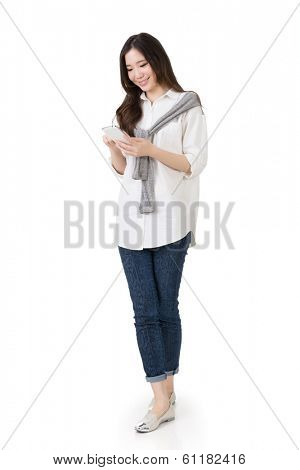 Attractive young Asian woman using cellphone to check message, full length portrait isolated on white background.