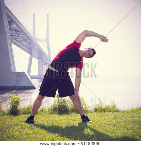 Athlete at the city  park warming and stretching