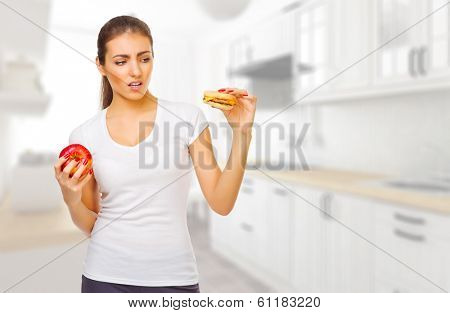 Young girl with hamburger and apple ay kitchen