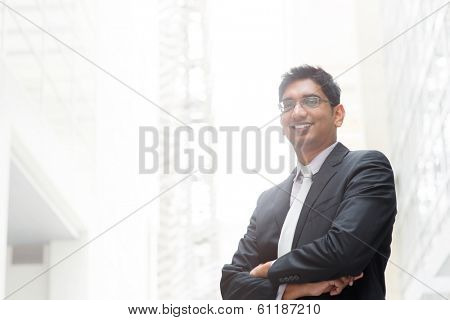 Portrait of happy and confident 30s Asian Indian businessman smiling. India male business man, real modern office building as background.