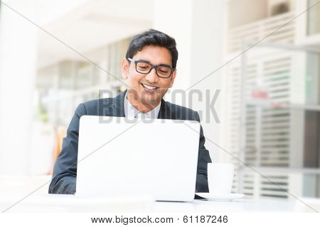 Young Asian Indian businessman using a notebook computer or laptop during office break at cafe, relaxing with a cup of coffee. India male business man, real modern office building as background.