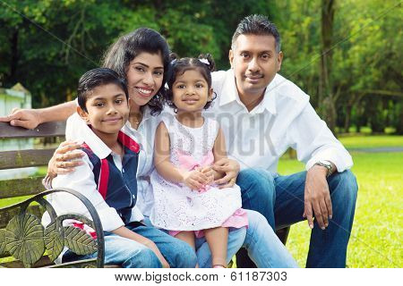 Happy Indian family at outdoor park. Candid portrait of parents and children having fun at garden park.