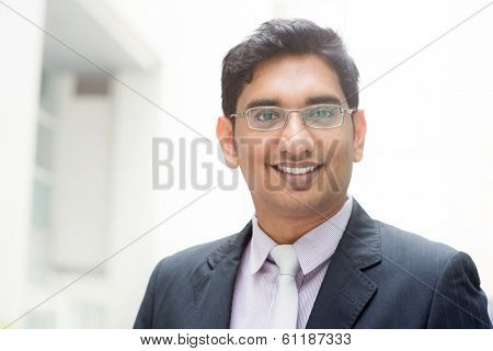 Portrait of confident 30s Asian Indian businessman smiling. India male business man, real modern office building as background.