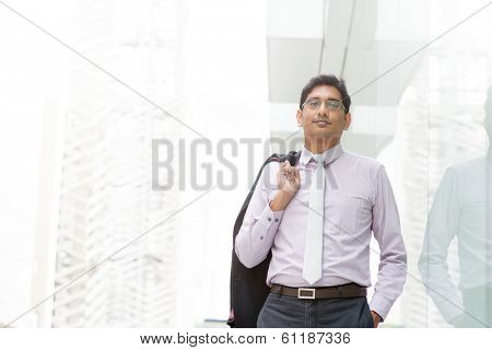 Candid portrait of 30s Asian Indian businessman walking outside office. India male business man, real modern office building as background with natural sunlight.