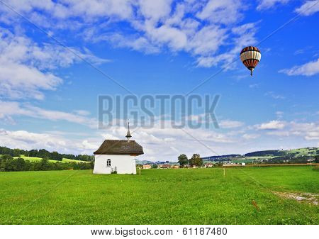 France, Haute Savoie. Adorable little chapel on the lawn. Above the chapel is flying scenic balloon