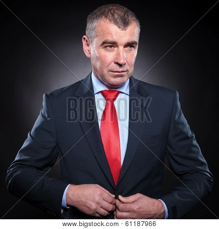 side view of an attractive mature elegant man unbuttoning his suit ad looks away from the camera