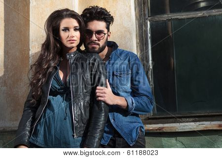 young casual couple posing outdoor on a sunny day, they are both looking into the camera