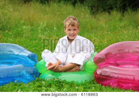 Karate Boy Sits In Inflatable Armchair  On Lawn