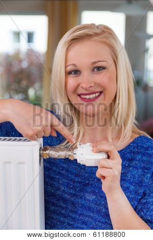 to conserve energy and electricity lowers the temperature of a young woman in the living room