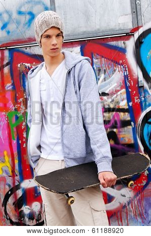 a cool-looking teenager man in front of graffiti