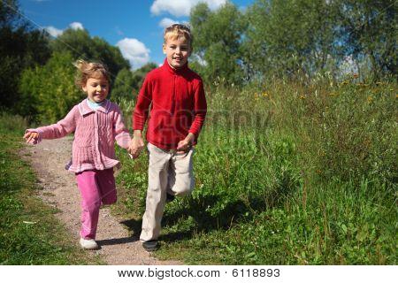 Two Children Run On Path In Summer