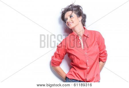 photo of a casual young woman with both hands at the back, smiling while looking away from the camera. leaning on white studio backgroud