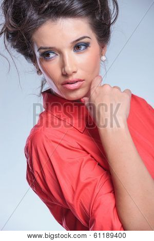close-up of a casual young woman holding her hand at her face and looking away from the camera while keeping a serious expression. on gray studio backgroud