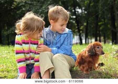 Kinder mit Dackel sitzen auf Gras
