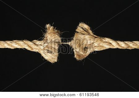 Fraying rope about to break on black background