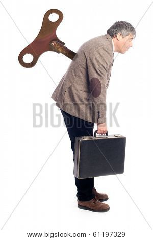 businessman with a wind up key in his back on white background