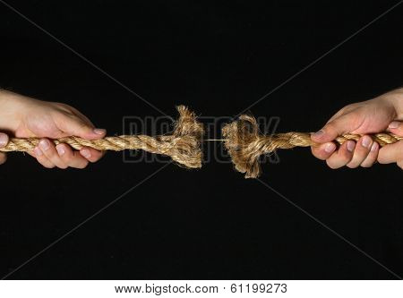 Two hands pulling frayed rope on black background