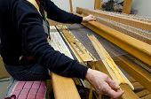 stock photo of loom  - Old Swedish handcraft creating a carpet in a loom - JPG