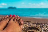 stock photo of sun tan lotion  - Womans Bare Feet over Sea background, blurred.
