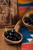 marinated Olives in old spoon with moroccan  ornament on wood, shallow dof