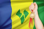 Medal In Hand With Flag On Background - Saint Vincent And The Grenadines