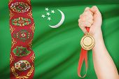 stock photo of turkmenistan  - Sportsman holding gold medal with flag on background  - JPG