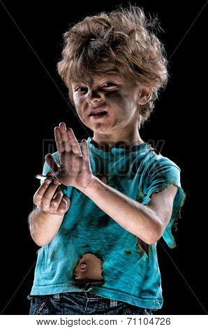 Portrait of burnt little boy with cigarette butt holding up his hand to say stop, over black background