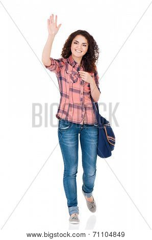 Smiling student girl with bag greets with her hand, isolated on white background