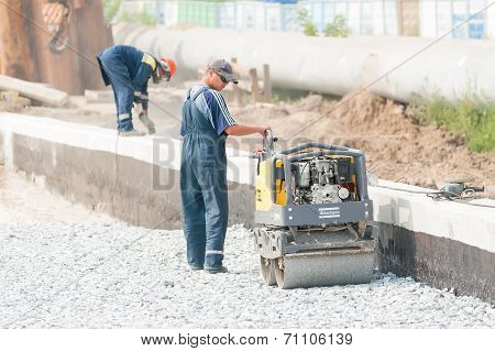 Worker stamps filling brick by skating rink