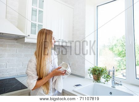 Woman Doing The Washing Up In The Kitchen