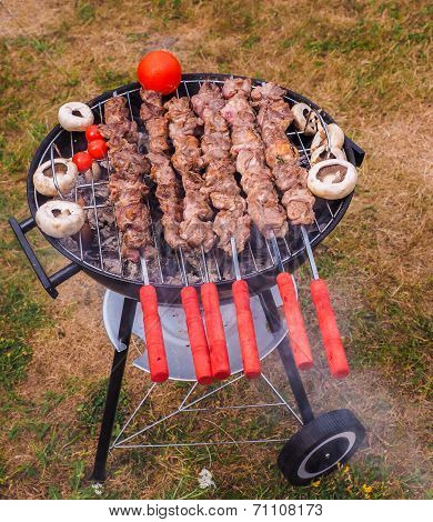 Shish Kebab Prepared Over A Black Round Shaped Charcoal Barbecue Outdoors