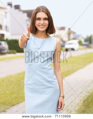 Young woman showing ok , standing near house