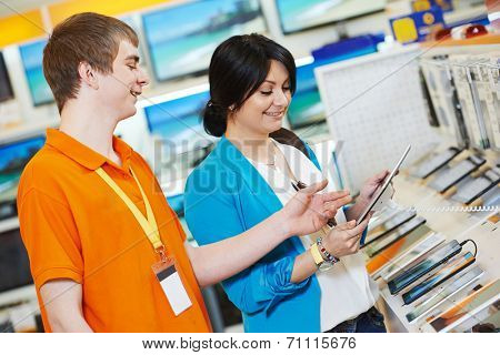Young woman choosing tablet pc computer set with shop assistant in home appliance shopping mall supermarket