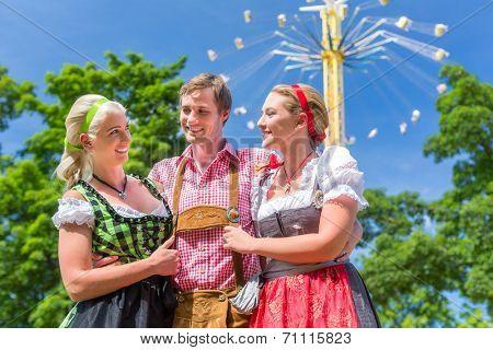 Women friends visiting Bavarian folk festival in  Dirndl standing in front of carousel
